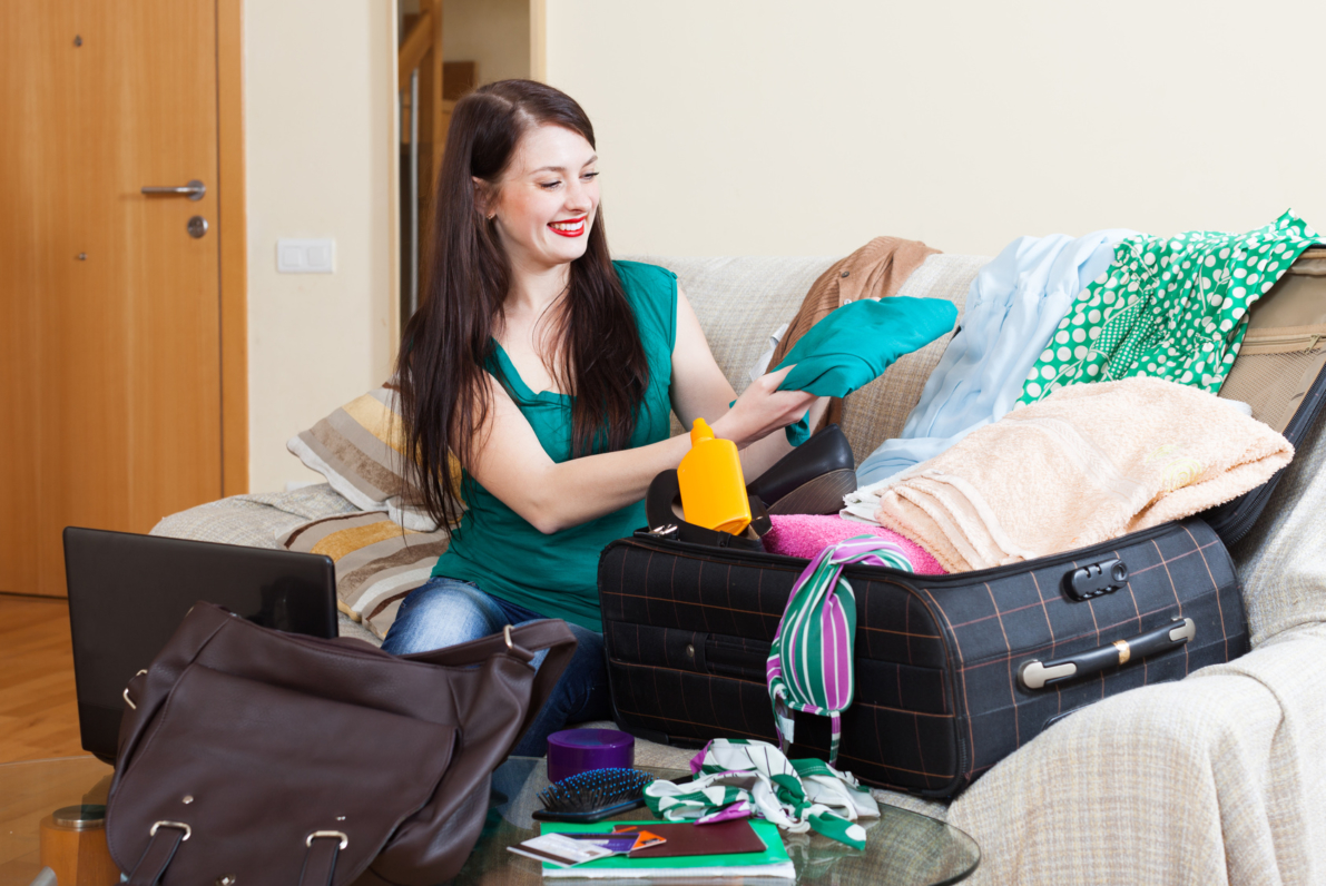 girl on sofa packing suitcase for holiday