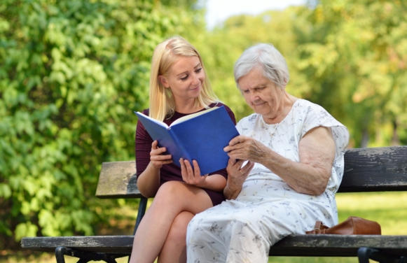 Young woman reading a book elderly woman in the park.