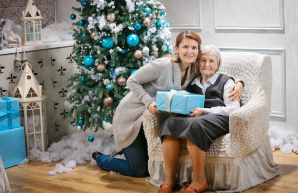 Senior woman and her adult granddaughter holding a gift against a Christmas tree