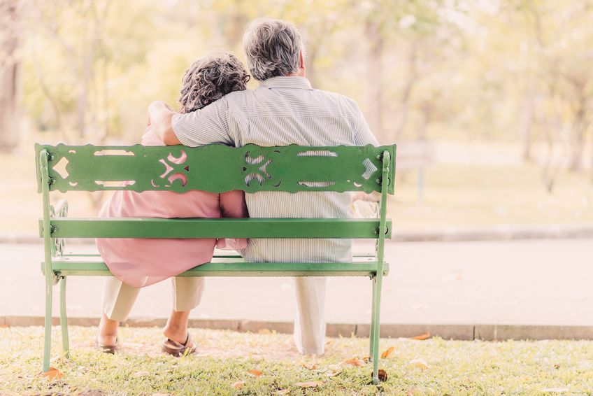 senior couple in love sitting on the bench in the park